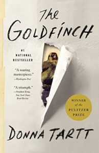 A goldfinch peeking through a ripped paper with the title and author in a handwritten font above and below