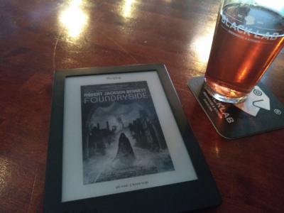 Ebook reader with said novel enjoying the Pub