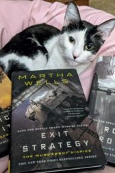 Black and white cat surrounded by three books, Artificial Condidtion, Exit Strategy, and Rogue Protocol