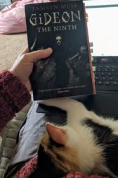 A picture of a the book Gideon the Ninth being held in front of a laptop, with a kitten curled up in the foreground..