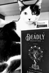 "Picture of a black and white cat sitting behind the book, ""Deadly Education""."