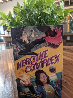 The book Heroine Complex by Sarah Kuhn sitting on a wooden table top with a leafy plant behind it.