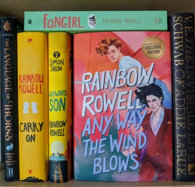 """Several books on a bookshelf with """"Any Way the Wind Blows"""" by Rainbow Rowell featured prominently"""