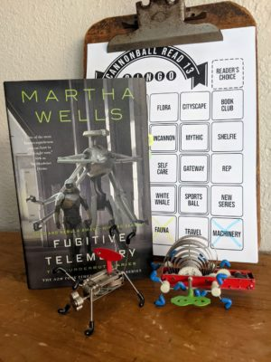The book Fugitive Telemetry is standing next to two wind up robot toys.