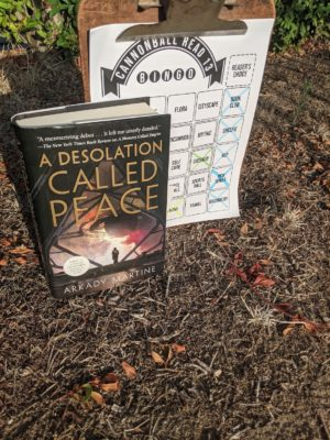 The book A Desolation Called Peace stands in front of a clipboard with a bingo sheet on it. The both are on dry ground with dead leaves and grasses.