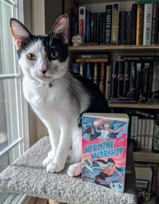 A black and white cat sitting next to the book Heroine Worship by Sarah Kuhn