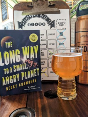 The book The Long Way to a Small, Angry Planet by Becky Chambers next to a pint glass of hard cider.