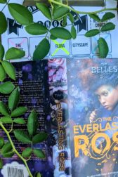 """The cover of the book """"The Everlasting Rose"""" by Dhonielle Clayton with branches of a rose bush above and to the side of the book."""