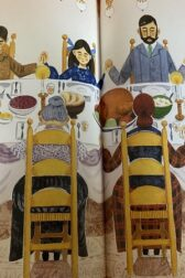 Illustration of oldfashioned family sitting around a large table, heads bowed in prayer