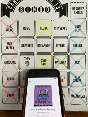A phone with the audio book Practical Demonkeeping open on the screen, with a bingo board behind the phone.