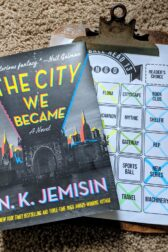 The book The City We Became by N.K. Jemisin lying on top of a clipboard holding a book bingo sheet